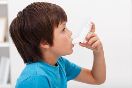 Junge mit Asthma benutzt einen Inhalator.