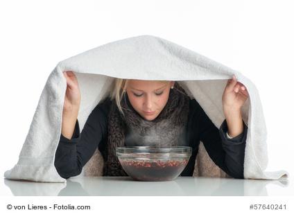 Kranke Frau inhaliert über einer Glasschale