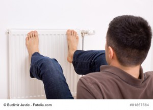 Young man heating his bare feet on radiator on wall