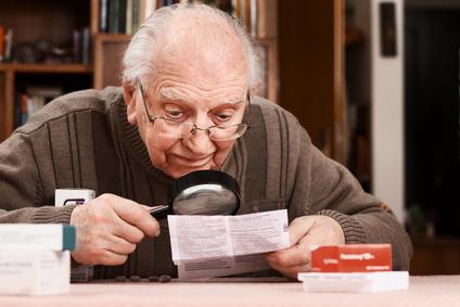 Älterer Herr liest Packungsbeilage aufmerksam