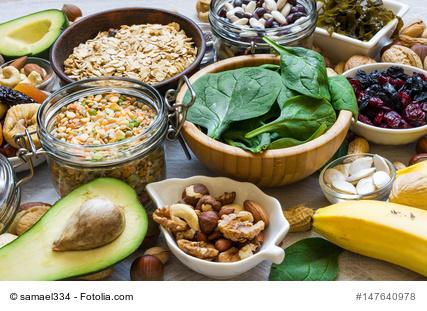 verschiedene Lebensmittel, die Kalium enthalten zum Beipsiel Nüsse, Bananen, Spinat und Avocado