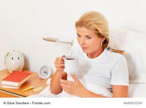 Frau sitzt im Bett und trinkt Tee