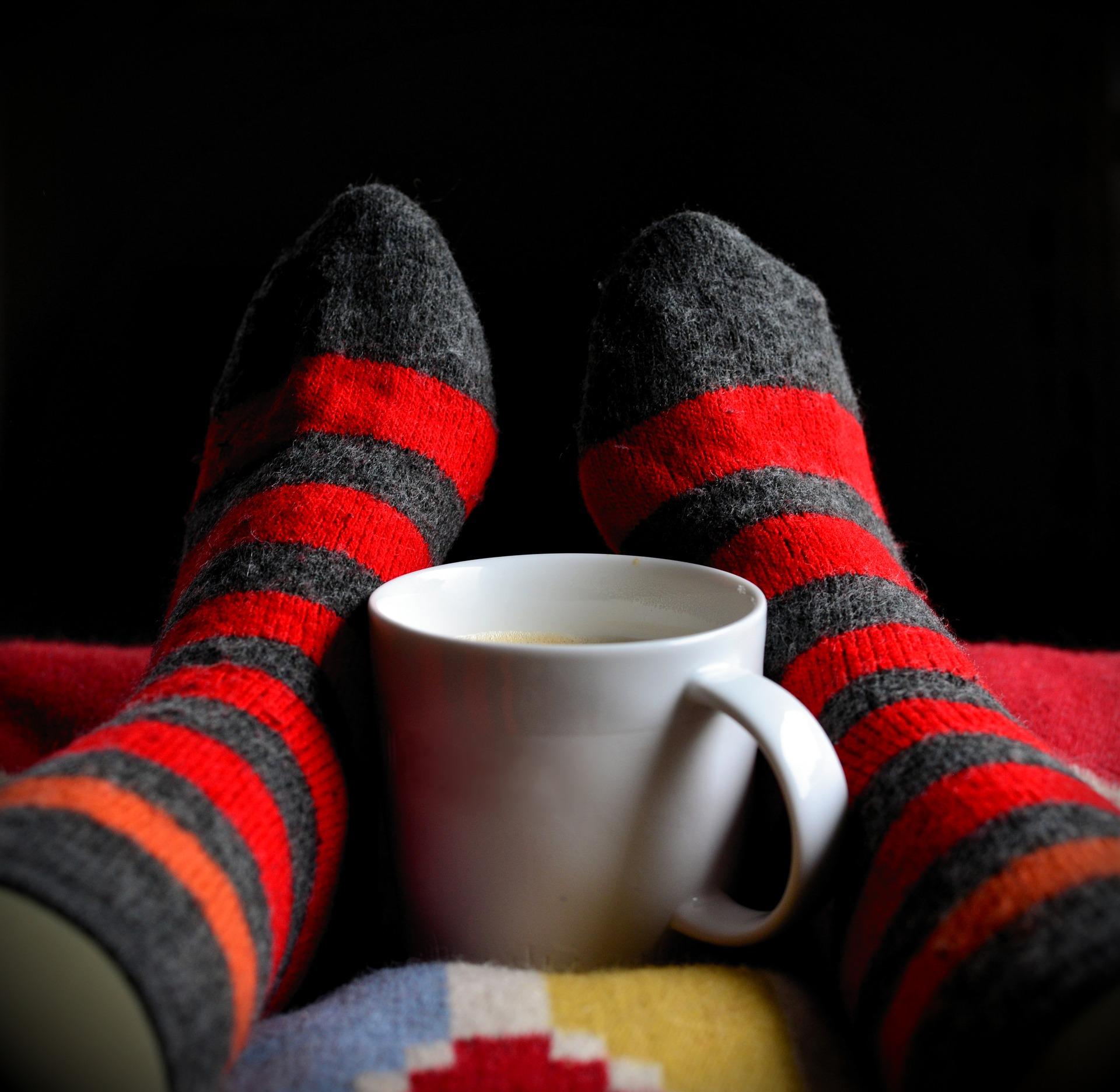 Füße in warmen Socken an einer Tasse mit Tee wärmen